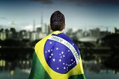 stock photo of democracy  - Man holding the brazilian flag in Ibirapuera Park - JPG