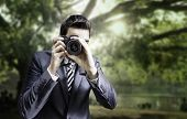 Male photographer focusing and composing an image with his professional digital SLR camera pointing the lens directly at the viewer in a park