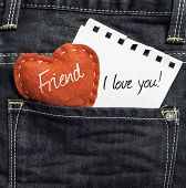 Friend I love you! written on a peace of paper and a heart on a jeans background