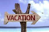 Vacation wooden sign with a beach on background