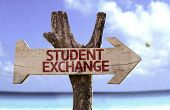 Student Exchange wooden sign with a beach on background