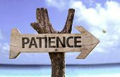 Patience wooden sign with a beach on background