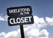 Skeletons in the Closet sign with clouds and sky background