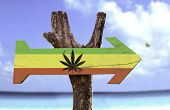 Rasta Flag With Marijuana Leaf sign with a beach on background