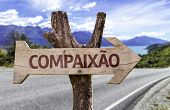 "image of compassion  - ""Compaixao"" (In portuguese: Compassion) wooden sign with a street background - JPG"