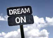 Dream On sign with clouds and sky background