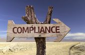 Compliance wooden sign with a desert background