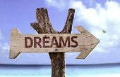 Dreams wooden sign with a beach on background