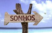 Dreams (In Portuguese) wooden sign with a beach on background