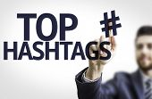 Business man pointing to transparent board with text: Top Hashtags