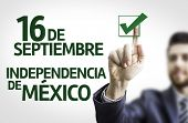Business man pointing to transparent board with text: 16 September, Mexico Independency (In Spanish)