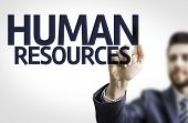 Business man pointing to transparent board with text: Human Resources