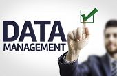 Business man pointing to transparent board with text: Data Management