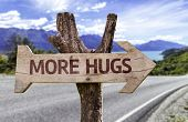 More Hugs wooden sign with a landscape background