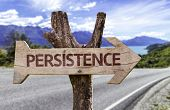 Persistence wooden sign with a road background