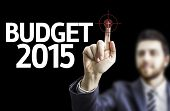 Business man pointing to black board with text: Budget 2015