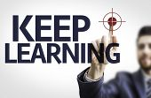 Business man pointing to transparent board with text: Keep Learning