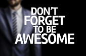 Don't Forget to Be Awesome written on a board with a business man on background