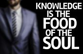 Knowledge is the Food of the Soul written on a board with a business man on background