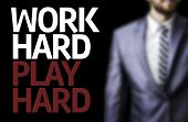 Work Hard Play Hard written on a board with a business man on background