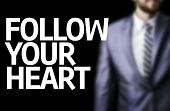 Follow your Heart written on a board with a business man on background