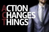 Action Changes Things written on a board with a business man on background