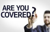 Business man pointing to transparent board with text: Are you Covered?