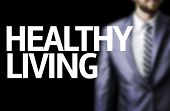 Healthy Living written on a board with a business man on background