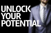 Unlock Your Potential written on a board with a business man on background