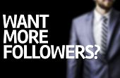 Want More Followers? written on a board with a business man on background