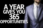 A year Gives You 365 Opportunities written on a board with a business man on background