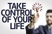 Business man pointing to transparent board with text: Take Control of Your Life
