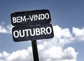 Welcome October (In Portuguese) sign with clouds and sky background