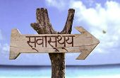 Health (In Hindi) wooden sign with a beach on background