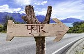 Love (In Hindi) wooden sign with a road background