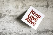 Keep Love Alive on Paper Note on texture background