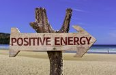 Positive Energy wooden sign with a beach on background