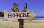 Exercise wooden sign with a beach on background