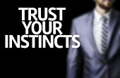 Business man with the text Trust your Instincts in a concept image