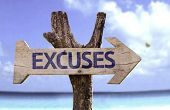 Excuses wooden sign with a beach on background
