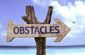 Obstacles wooden sign with a beach on background