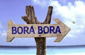 Bora Bora wooden sign with a beach on background