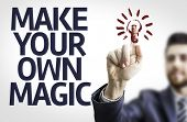 Business man pointing to transparent board with text: Make Your Own Magic