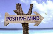 Positive Mind wooden sign with a beach on background