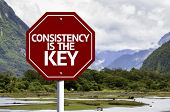 Consistency is The Key written on red road sign with landscape background