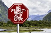 Big Journeys Begin With Small Steps written on red road sign with landscape background