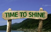 Time To Shine wooden sign with a beach on background