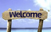 Welcome wooden sign with a beach on background
