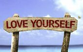 Love Yourself wooden sign with a beach on background