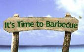 It's Time to Barbecue wooden sign with a beach on background